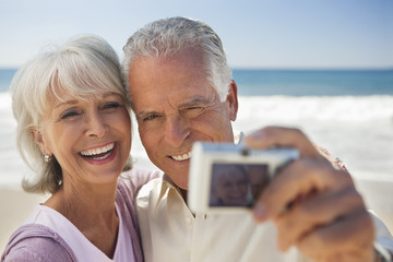 smiling senior couple taking self-portrait with digital camera on beach