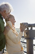 smiling senior couple using coin-operated binoculars