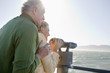smiling senior couple looking at ocean with coin-operated binoculars