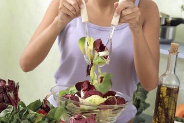 jeune femme remuant la salade avec des cuillères