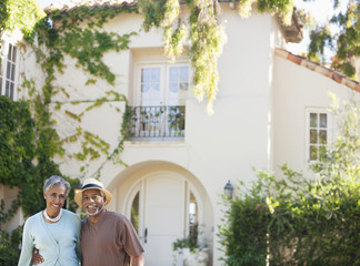 smiling senior couple outside house