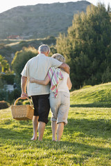 senior couple hugging and carrying picnic basket on grass