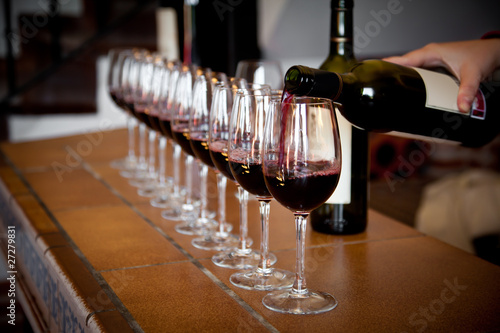 hand with wine bottle filling a row of glasses for tasting