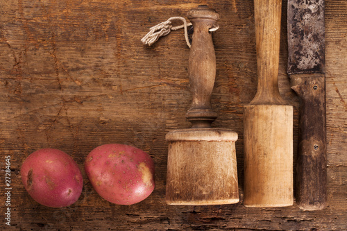 antique potato mashers and knife on  old wooden table with red