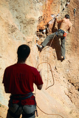 Two rock climbers, one belaying