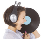 Profile of emotional brunette in headphones with vinyl record ov poster