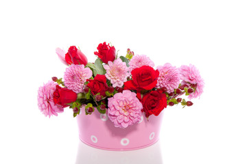 red and pink bouquet in a pink iron bucket isolated over white