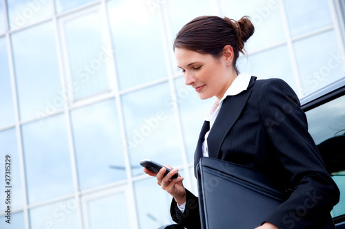 Young business woman outside, reading sms