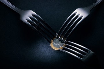 Three forks fighting over one euro coin,crisis competition
