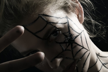 Beautiful young girl with the cobweb on the face