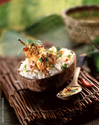 Chicken brochette with coconut milk rice in a coconut shell