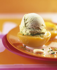 Half a peach topped with a scoop of pistachio ice cream