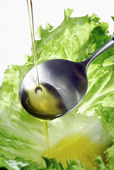 Pouring a drop of olive oil onto a lettuce leaf