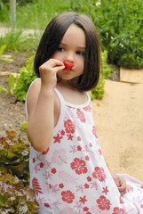 Young girl smelling a strawberry