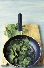 Cooking the spinach in a frying pan