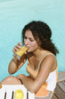 Woman drinking an apple juice by the swimming pool