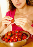 Woman taking the peduncles off the tomatoes