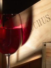 Glass of red wine and a wooden box Bacchus