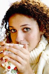 Woman drinking a hot cup of infusion or tea