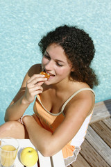 Woman eating a biscuit by the swimming pool