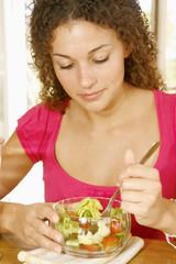 Woman eating an endive and tomato salad