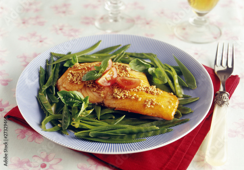 Half-cooked piece of salmon caramelized with soya sauce,honey,sesame seeds and sugar peas