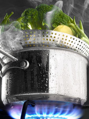 Steam cooking vegetables in a saucepan on a gas cooker