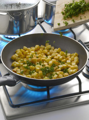 Adding chopped parsley to the frozen diced potatoes in the frying pan