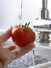 Rinsing a tomato under the tap water