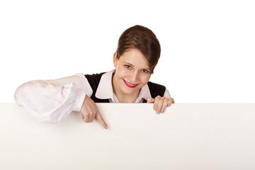 Junge Frau zeigt mit Finger auf leere Werbetafel / Reklame