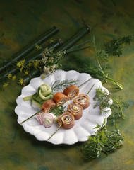 Sliced smoked salmon rolls on skewers