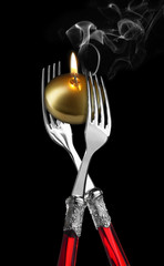 Two forks with golden candle ;candle light diner