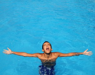 boy teenage relaxed open arms blue swimming pool