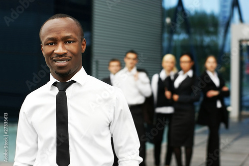 A young African American businessman in front of his colleagues