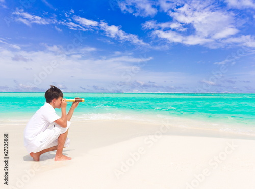 Boy with telescope on beach