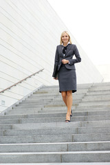A young blond businesswoman is walking on the stairs