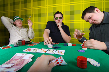 Three equal young men playing poker