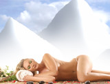 A young blond girl is lying on a spa treatment procedure