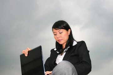 Asian girl outdoors with laptop.
