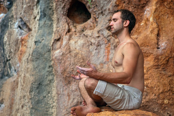 Young man meditating on rock in the mountains