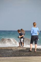 Mutter mit Sohn und Tochter blicken auf die Brandung am Meer