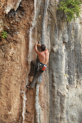 Male rock climber moving up the cliff