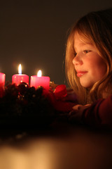 Mädchen schaut auf Adventskranz