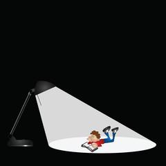 Desk lamp illuminating a boy reading
