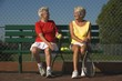 Two Senior Women Sitting With Tennis Rackets