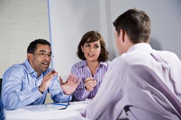 Three mid-adult people sitting at table meeting