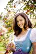 Frau mit Glas in Tracht vor Apfelbaum