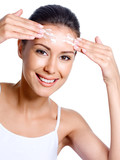 Happy woman applying cream on her forehead poster