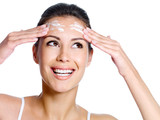 Woman with cream on the forehead looking up poster
