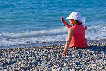 a woman with a camera on the coast
